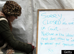 A woman closes a tent at the 'Occupy London' camp site outside St Paul's Cathedral on December 19, 2011 in London, England. A four day trial to determine whether Occupy London protesters can stay on the land outside St Paul's Cathedral will begin today at the High Court. (Getty)