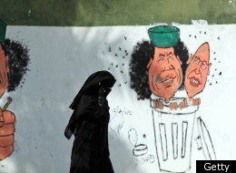 A Libyan woman walks past graffiti depicting ousted leader Muammar Gaddafi and his son Seif al-Islam in Tripoli on October 12, 2011. (Getty)