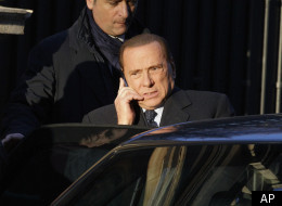 Italian former premier Silvio Berlusconi talks on a cellphone as he leaves his house during a break of the Berlusconi Mills trial, in Milan, Thursday, Dec.22, 2011. (AP)