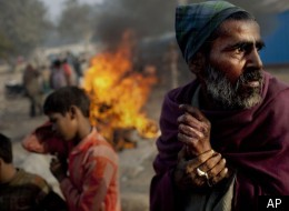 An Indian man stands near his belongings as they were burned by police who evicted him from squatting, on a street in New Delhi, India, Thursday, Dec. 22, 2011. Though India is famous for its brutally hot summers, temperatures fall sharply for a few weeks in December and January. Poor people, particularly those living on the streets, are the worst hit. (AP Photo/Kevin Frayer)
