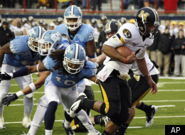 Missouri quarterback James Franklin, right, dodges North Carolina defenders on his way to a first quarter two-yard touchdown run during the Independence Bowl college football game, Monday, Dec. 26, 2011, in Shreveport, La. (AP Photo/Rogelio V. Solis)