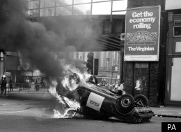 A police car in flames after riots in Brixton which Thatcher feared could ruin the Royal wedding of Diana and Charles