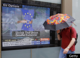 A man holding an umbrella passes by a TV screen showing a Bloomberg television channel's news program in a window on September 12, 2011 in Paris. (Getty)