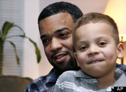 """In this Dec. 27, 2011 photo, Damon Brown sits with his son Julian, 5, at their home in Seattle. Damon Brown found a kidney on Facebook after telling his story on a special page the Seattle dad created under the name, """"Damon Kidney."""" His friends and family forwarded the link to everyone they knew and on Jan. 3, a woman his wife has known for years but not someone they consider a close family friend, will be giving him a kidney. (AP Photo/Elaine Thompson)"""