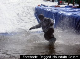 A snowboarder crosses the watery finish line at Ragged Mountain Resort.