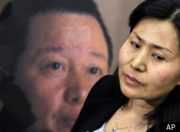 Geng He, wife of disappeared Chinese human rights lawyer Gao Zhisheng, seen on poster at rear, is interviewed in Washington, Tuesday, Jan. 18, 2011. (AP)