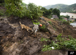 A firefighter takes a dog downhill at the site of a mudslide to search for missing people in Jamapara, Rio de Janeiro state, Brazil, Tuesday, Jan. 10, 2012. (AP)