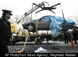 People gather around a car as it is removed by a mobile crane in Tehran, Iran, Wednesday, Jan. 11, 2012. Two assailants on a motorcycle attached magnetic bombs to the car of an Iranian university professor working at a key nuclear facility, killing him and wounding two people on Wednesday, a semiofficial news agency reported.