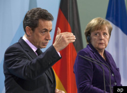 French President Nicolas Sarkozy with German Chancellor Angela Merkel. French officials have said they will implement cost-cutting measures in the wake of Friday's credit downgrade.