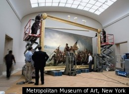 Staff at the Metropolitan Museum of Art hang the newly framed and restored