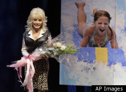 Dolly Parton announces plans on Thursday, Jan. 19, 2012, to open a water-snow park in Nashville, Tenn. The $50 million park is described as the first of its kind in the country and is projected to open as early as summer 2014. Parton holds flowers because it is also her 66th birthday. (AP Photo/Mark Humphrey)