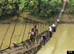 Indonesian children cling onto the rails to cross the river