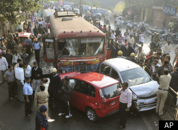 Indians look at a damaged vehicles at the scene where a bus was driven into numerous vehicles and pedestrians in the city of Pune, central India, Wednesday, Jan. 25, 2012. (AP)