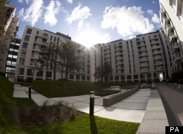 In this photo taken with a fish-eye lens, the sun shines above structurally completed apartments at the Olympic Village in the Olympic Park in east London,