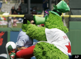 The Philadelphia Phillies mascot the Phillie Phanatic kisses third base umpire Phil Cuzzi between innings against the Cleveland Indians during a Grapefruit League spring training baseball game in Clearwater, Fla., Monday, March 17, 2008. (AP Photo/Paul Sancya)
