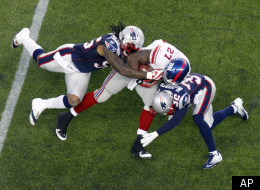 New England Patriots' Brandon Spikes, left, and Devin McCourty, right, tackle New York Giants running back Brandon Jacobs in the first quarter of an NFL football game in Foxborough, Mass., Sunday, Nov. 6, 2011. (AP Photo/Michael Dwyer)