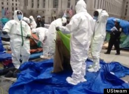 Work crews in white biohazard suits inspected tents in Freedom Plaza on Sunday afternoon. Some tents were found to be not in compliance and were dismantled.