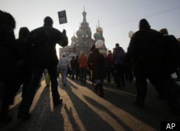 Demonstrators march during a massive protest against Prime Minister Vladimir Putin's rule in St. Petersburg, Russia, Saturday, Feb. 4, 2012, with the Savior of Spilled Blood Cathedral on the background. (AP)