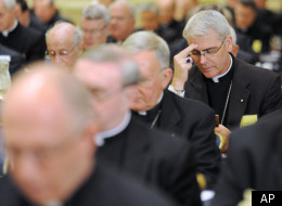 Bishop Paul Coakley, right, of Salina, Kan., prays during the U.S. Conference of Catholic Bishops' annual fall meeting in 2010 in Baltimore.