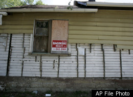 A realty sign rests on a vacant house in Cleveland stripped of its aluminum siding. In the county that contains Cleveland, about 1 in 10 homes are vacant. Most vacancies are due to a pending or complete foreclosure.