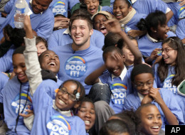 Denver Broncos quarterback Tim Tebow is surrounded by children as he visits the Boys & Girls Club in Los Angeles on Monday, Feb. 13, 2012. Tebow read a book, and encouraged children to read. (AP Photo/Nick Ut)