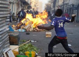 Un manifestant jette une pierre à Dakar, le 18 février 2012