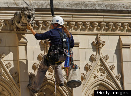 Katie Francis, a member of the Difficult Access Team from Wiss, Janney, Elstner Associates, inspects a gargoyle while rapelling down one of the north tower on the west front of the National Cathedral while looking for damage from August's magnitude 5.8 earthquake and high winds from Hurricane Irene October 17, 2011 in Washington, DC. DAT members used cameras, cell phones and iPad computers to record places on the cathedral's west front where damage was apparent. (Photo by Chip Somodevilla/Getty