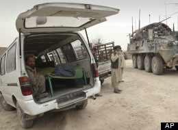 An armored military vehicle from the NATO-led International Security Assistance Force (ISAF) is seen at right, as the covered body of a person who was allegedly killed by a U.S. service member is seen inside a minibus in Panjwai, Kandahar province. (AP Photo/Allauddin Khan)