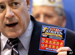 Illinois Gov. Pat Quinn shows off the Veteran's Cash scratch-off lottery ticket, the Stars & Stripes, in Springfield, Ill.