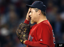 Boston Red Sox pitcher Bobby Jenks wipes his face after giving up an RBI double to Seattle Mariners Jack Cust in the seventh inning of an MLB baseball game in Boston, Friday, April 29, 2011. (AP Photo/Charles Krupa)