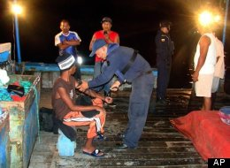 In this photo released by Ecuador's navy, Panamanian fisherman Adrian Vasquez, bottom left, an 18-year-old Panamanian who worked as a maid in a seaside resort hotel, receives medical attention aboard a fisherman boat offshore Galapagos Islands, Ecuador, on March 25. (AP Photo/Ecuador's navy)