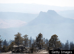 In this aerial photograph, vehicles sit burned out amid the remnants of a destroyed structure in the wake of the Lower North Fork Wildfire as it burns in the foothills community of Conifer, Colo., southwest of Denver on Tuesday, March 27, 2012. Firefighters are now able to actively battle the blaze on the ground that started on Monday and has already destroyed at least 16 homes in the rugged terrain. (AP Photo/David Zalubowski)