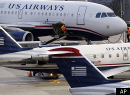 In this July 19, 2011 photo, baggage is unloaded from a U.S. Airways jet at Logan International Airport in Boston.