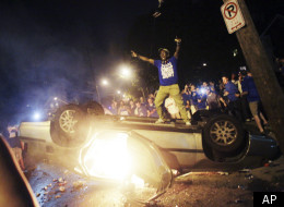 In this Saturday, March 31, 2012, photo, a Kentucky fan cheers on top of a car as people celebrate Kentucky's 69-61 win over Louisville in an NCAA Final Four semifinal college basketball tournament game in Lexington, Ky. Lexington police say they are prepared to control crowds near the University of Kentucky's Lexington campus when Kentucky plays Kansas in the national championship basketball game on Monday. (AP Photo/Christian Randolph)