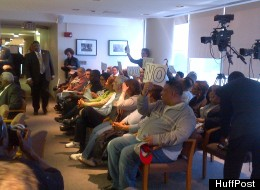 Audience members at a Detroit City Council meeting April 2, 2012, hold signs protesting a possible financial consent agreement between the city and state of Michigan.