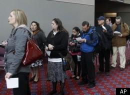 In this March 7, 2012 file photo, job seekers stand in line during the Career Expo job fair in Portland, Ore.