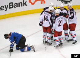 The Columbus Blue Jackets celebrate a goal by Rick Nash as Colorado Avalanche defenseman Shane O'Brien, left, kneels on the ice in the second period of an NHL hockey game on Thursday, April 5, 2012, in Denver. (AP Photo/Chris Schneider)