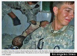 Deux soldats américains en uniforme, dont un souriant au premier plan, près d'un corps d'un afghan en 2010, Los Angeles Times