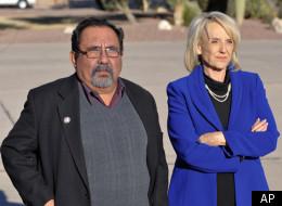 Arizona Gov. Jan Brewer (R) and Rep. Raul Grijalva (D-Ariz.) await the arrival of President Barack Obama on Jan. 12, 2011.