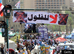 Egyptians sit on a traffic light decorated with a banner showing the portraits of former prime minister Ahmed Shafeq (R) and former Arab League general secretary Amr Mussa during a rally in Cairo's Tahrir Square on April 20, 2012, to protest against the ruling military and hold-overs from the former ruling government ahead of the presidential election to be held at the end of May. (KHALED DESOUKI/AFP/Getty Images)