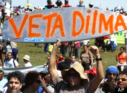 A demonstrator holds up a surfboard spray painted with a message in Portuguese that reads: