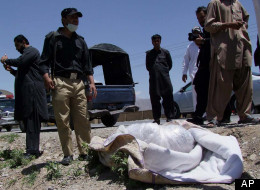 Pakistani security officials stand next to covered body of British Red Cross worker Khalil Rasjed Dale at the site in Quetta, Pakistan on Sunday, April 29, 2012. (AP Photo/Arshad Butt)