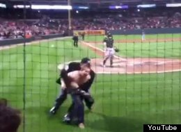 The home plate umpire tackles a fan running on the field during an Orioles-A's game.