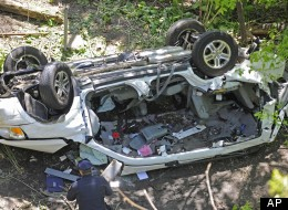 Police investigate the destroyed van that plunged over the Bronx River Parkway, Sunday April 29, 2012, in New York. (AP Photo/ Louis Lanzano)