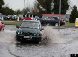 A car drives through a puddle near Epsom, Surrey