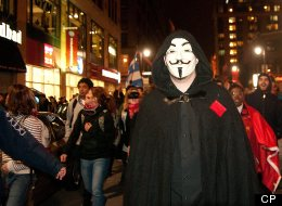 Protester wearing a Guy Fawkes mask in another nightime protest on Montreal city streets.