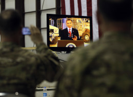 Military personnel watch on a screen as President Barack Obama makes a live address at Bagram Air Field, Afghanistan, Wednesday, May 2, 2012. (AP Photo/Charles Dharapak)