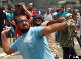 Egyptian anti-military protesters throw stones during clashes with unidentified attackers in the Abbassiya district of Cairo on May 2, 2012. (KHALED DESOUKI/AFP/GettyImages)