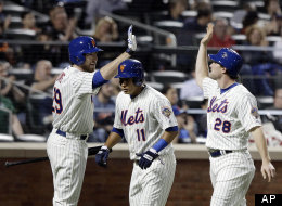 New York Mets' Ike Davis, left, celebrates with teammates Daniel Murphy (28) and Ruben Tejada (11) after they scored on a Scott Hairston double against the Arizona Diamondbacks, Friday, May 4, 2012, in New York.