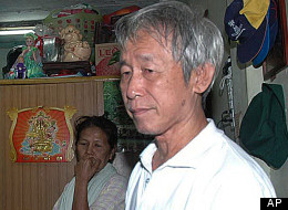 In this photo taken Aug. 3, 2010, Amphon Tangnoppakul, right, pauses as he is arrested by Thai police officers of defaming Thailand's royal family in mobile phone text messages at his house in Bangkok, Thailand. Amphon, who became known as